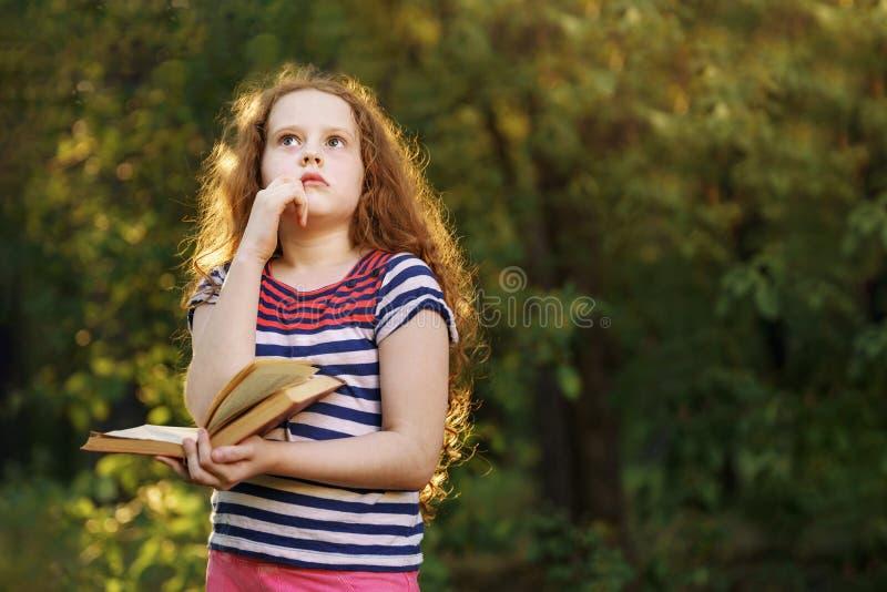 Peinzend meisje wat betreft kin met het denken uitdrukkingsgezicht stock foto
