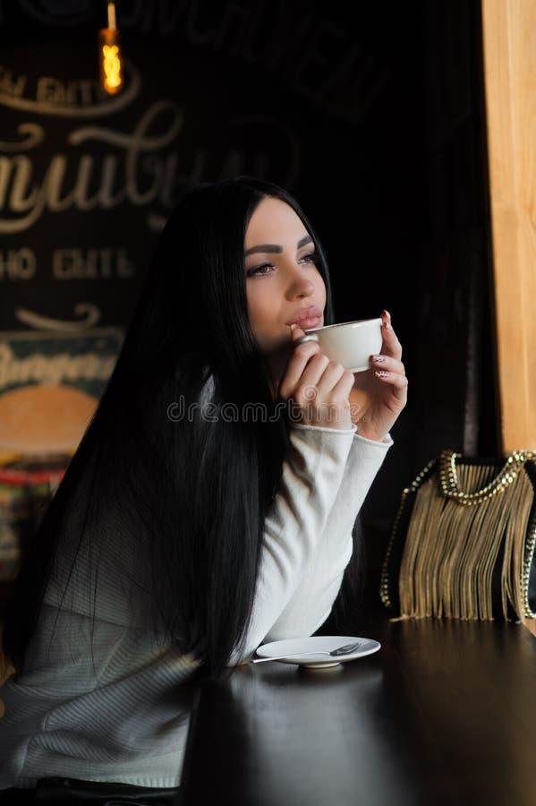 Peinzend mooi brunette in koffie met kop van koffie stock foto