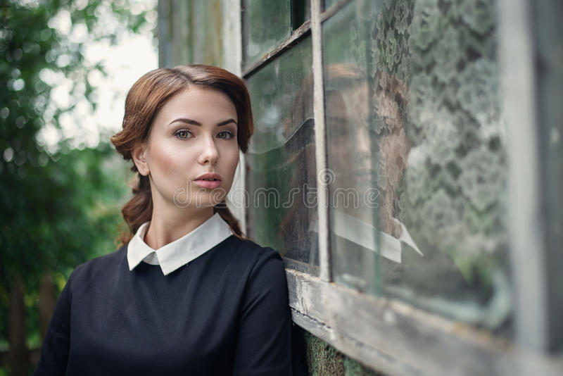 Peinzend mooi jong meisje in retro stijlkleding die zich dichtbij het venster van oud blokhuis bevinden stock afbeeldingen