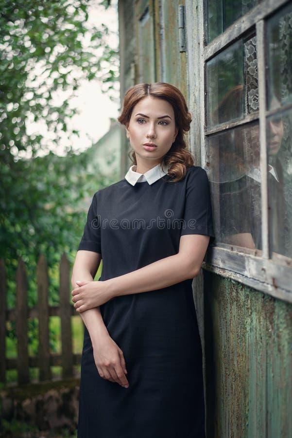 Peinzend mooi jong meisje in retro stijlkleding die zich dichtbij het venster van oud blokhuis bevinden royalty-vrije stock foto