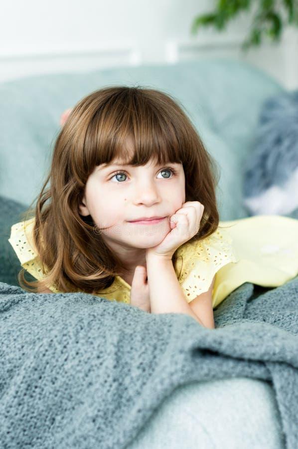 Peinzend portret van een klein meisje met blauwe ogen op de laag royalty-vrije stock foto's