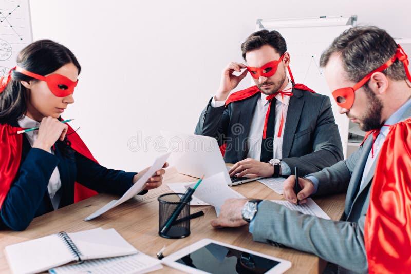 peinzend super zakenlui in maskers en kaap het werken stock foto's