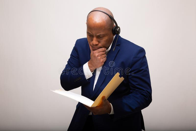 Peinzende Afrikaanse Amerikaanse Zakenman Looks Through File stock fotografie