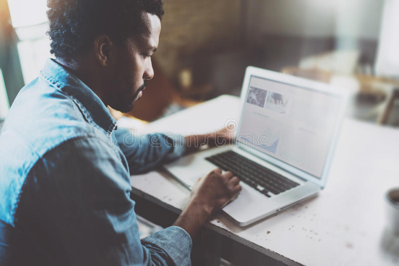 Peinzende Afrikaanse mens die aan laptop werken terwijl thuis het doorbrengen van tijd Concept jonge bedrijfsmensen die mobiele a stock fotografie