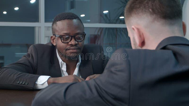 Peinzende Afro-Amerikaanse en Kaukasische zakenlieden die door documenten werken en financieel verslag bespreken die hebben royalty-vrije stock afbeeldingen