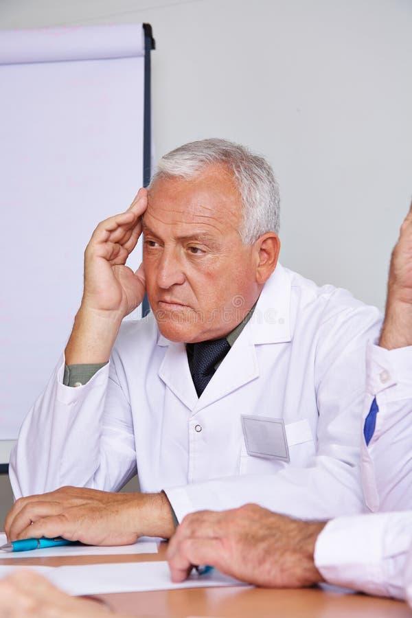 Peinzende arts in een vergadering royalty-vrije stock afbeeldingen