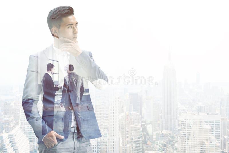 Peinzende Aziatische zakenman in een mistige stad royalty-vrije stock foto's