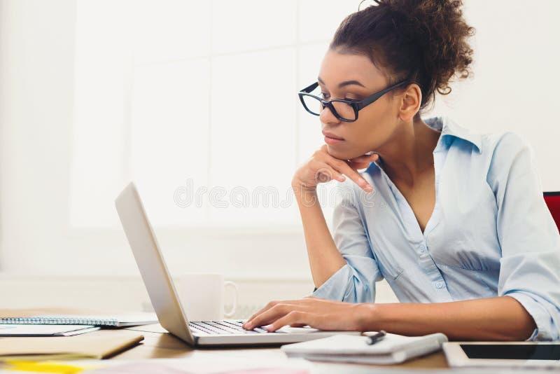 Peinzende bedrijfsvrouw die aan laptop op kantoor werken stock foto