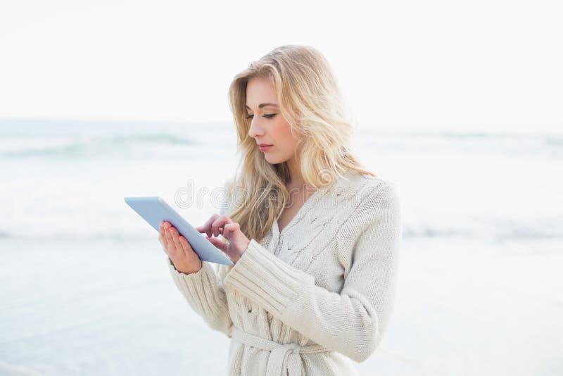 Peinzende blondevrouw in wolcardigan die een tabletpc met behulp van royalty-vrije stock foto