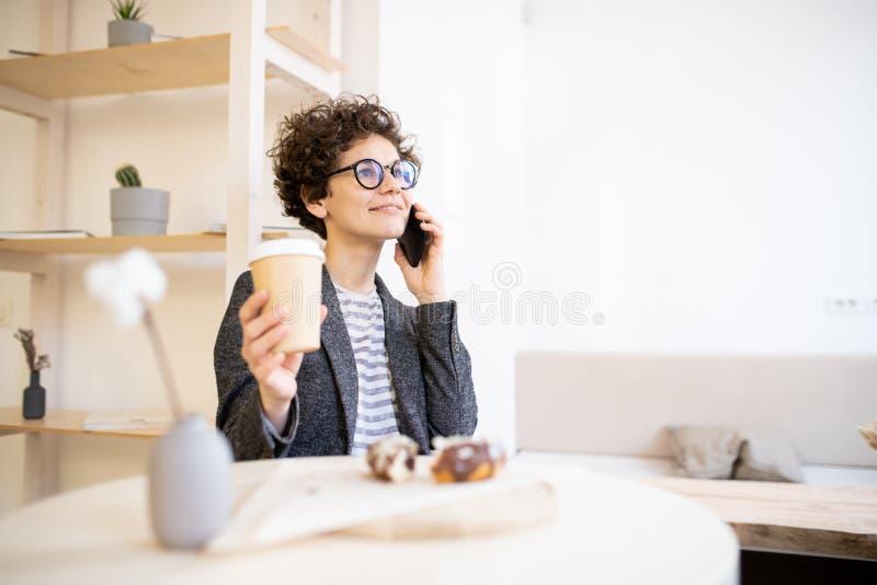 Peinzende dame die telefoon in koffie uitnodigt royalty-vrije stock afbeeldingen