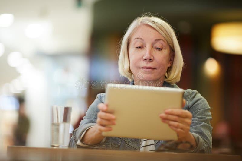 Peinzende dame het letten op video op tablet royalty-vrije stock afbeelding