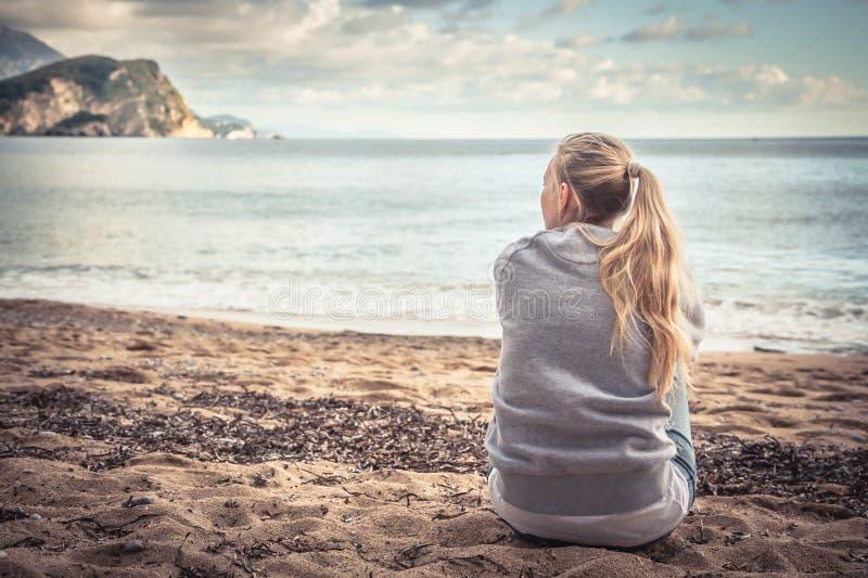 Peinzende eenzame jonge vrouwenzitting op strand die haar knieën koesteren en de afstand met hoop onderzoeken stock foto