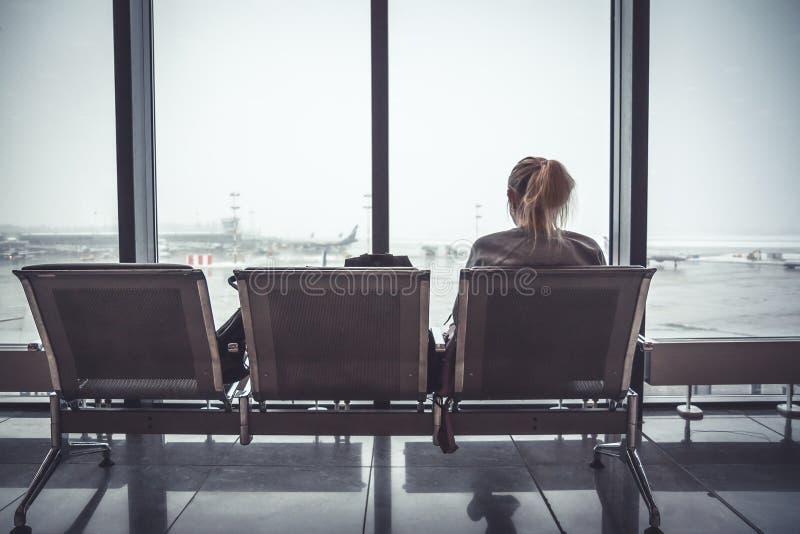 Peinzende eenzame vrouwentoerist in luchthaven eindzitting op stoel en het kijken op vliegtuigen door venster in vertrekholding z royalty-vrije stock afbeelding