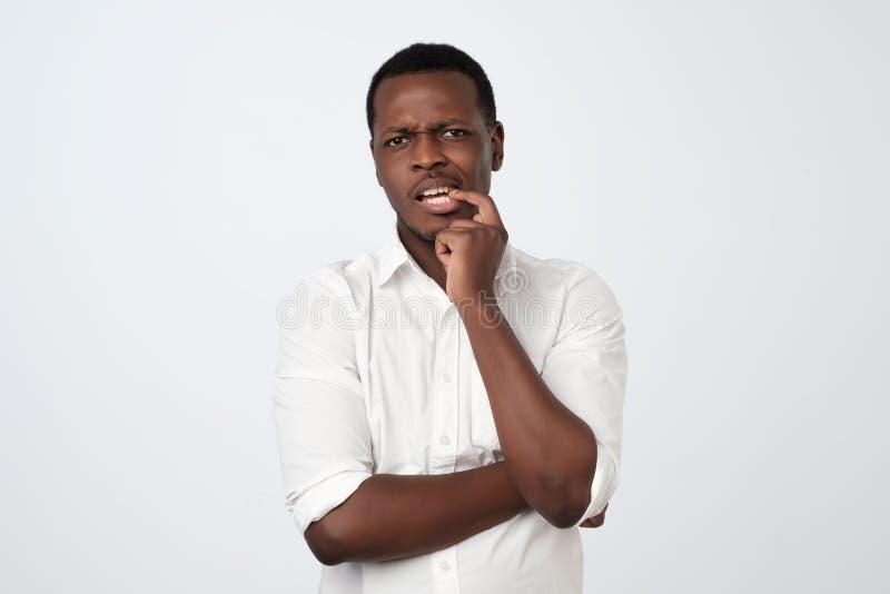 peinzende ernstige in verwarring gebrachte Afrikaanse Amerikaanse mens wat betreft zijn kin, die nadenkend en sceptisch over iets royalty-vrije stock foto's