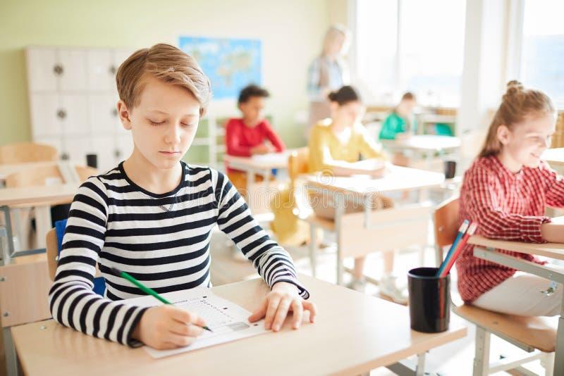 Peinzende geconcentreerde student bij geschreven test royalty-vrije stock afbeelding