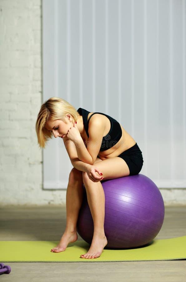 Peinzende geschikte vrouwenzitting op fitball stock afbeeldingen
