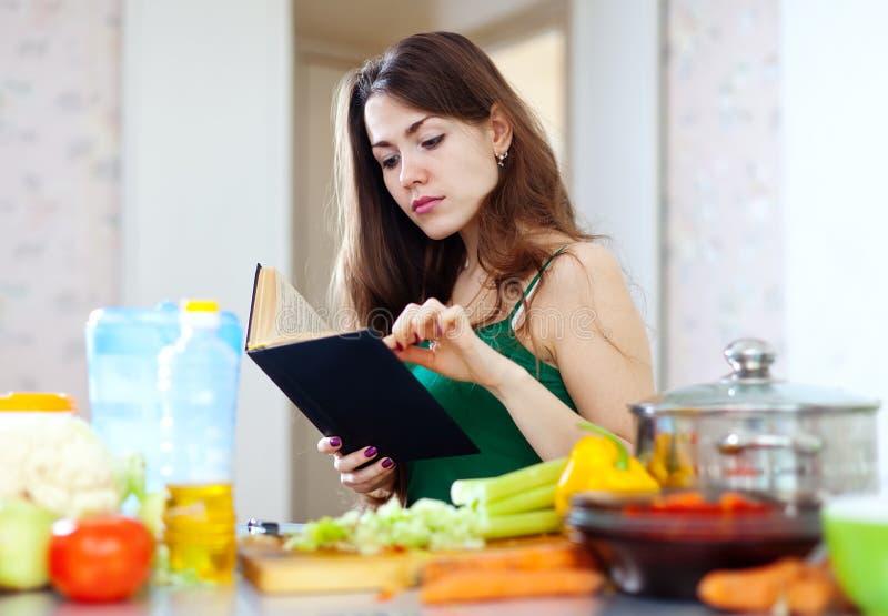 Peinzende huisvrouw met kookboek stock foto