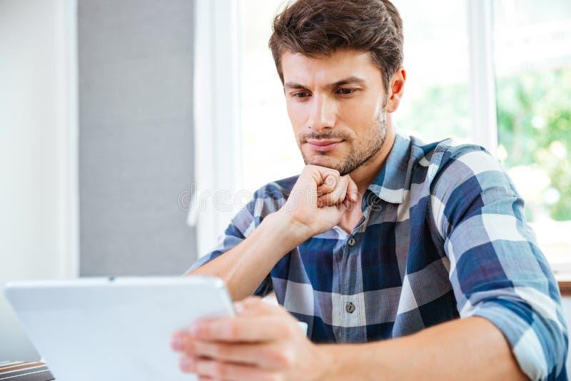 Peinzende jonge mens die en tablet thuis denken gebruiken royalty-vrije stock foto