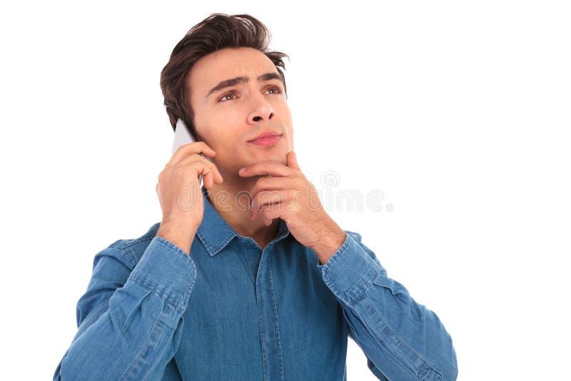 Peinzende jonge toevallige mens die op de telefoon spreken royalty-vrije stock afbeeldingen
