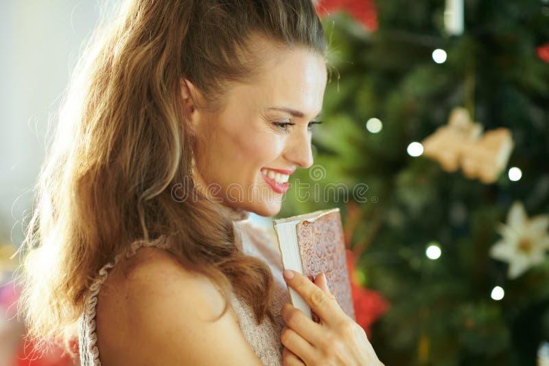 Peinzende jonge vrouw dichtbij Kerstboom die notitieboekje omhelzen royalty-vrije stock afbeelding