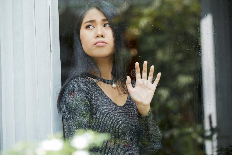 Peinzende jonge vrouw die door venster kijken royalty-vrije stock afbeelding