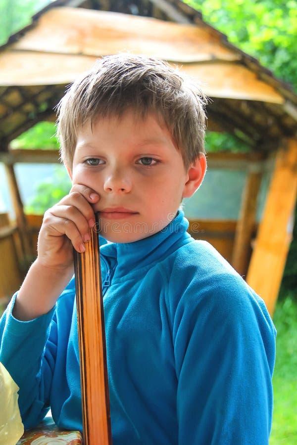 Peinzende jongen in de zomer houten gazebo stock fotografie