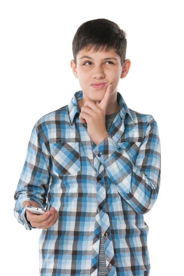 Peinzende jongen met een celtelefoon stock foto's