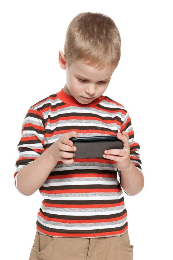 Peinzende jongen met een smartphone stock foto