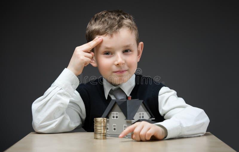 Peinzende jongen met huismodel en stapel van muntstukken stock fotografie