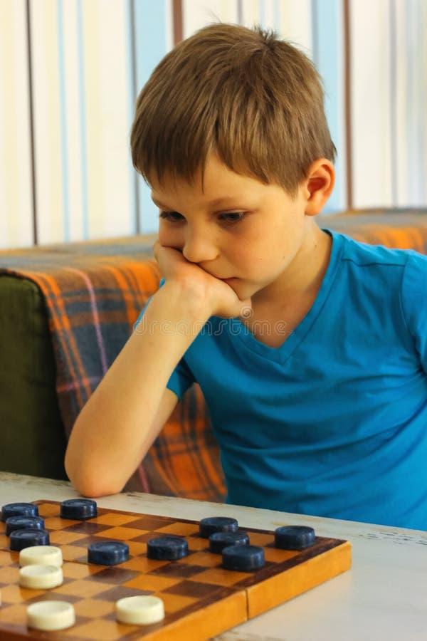 Peinzende jongen tijdens een spel van controleurs royalty-vrije stock fotografie