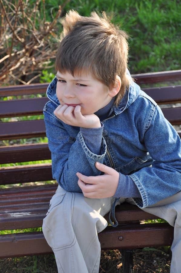 Peinzende jongenszitting op een parkbank stock fotografie