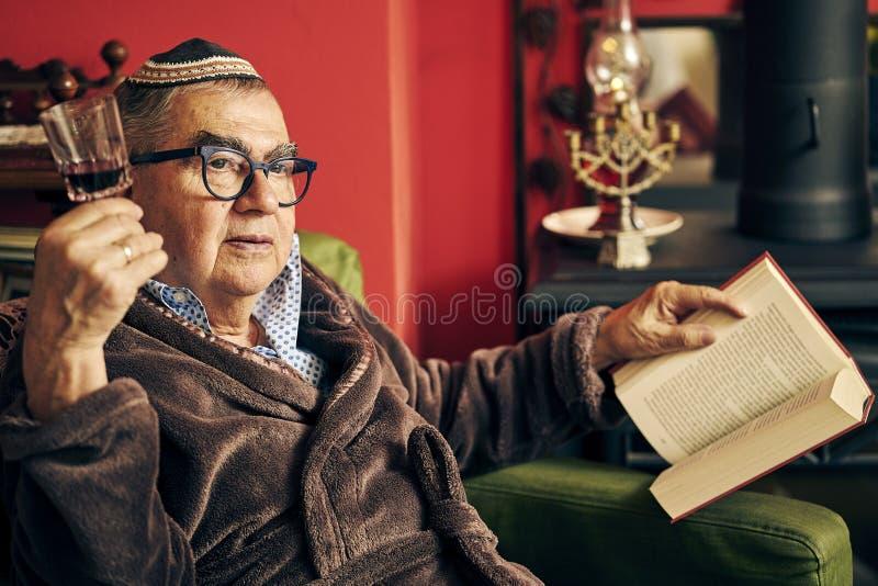 Peinzende Joodse oudste die een torahboek lezen en kosjer wijn drinken stock foto's