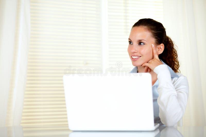 Peinzende Kaukasische jonge vrouw die net kijkt stock fotografie
