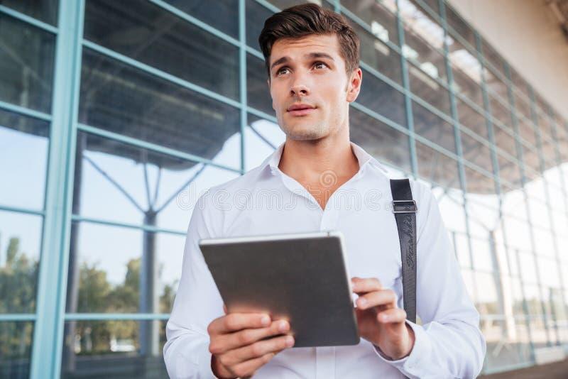 Peinzende knappe jonge zakenman die en tablet bevinden zich gebruiken royalty-vrije stock fotografie