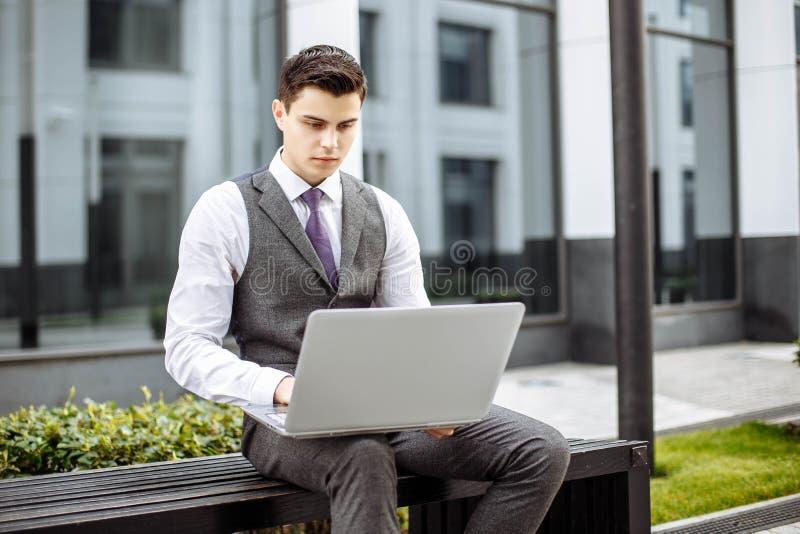 Peinzende knappe jonge zakenman die laptop in de stad met behulp van stock foto