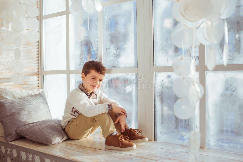 Peinzende leuk weinig jongen zit op een vensterbank in Kerstmistijd stock foto
