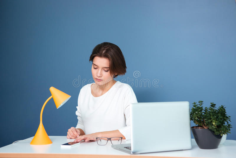 Peinzende leuke vrouw die en mobiele telefoon op werkplaats zitten met behulp van stock afbeelding