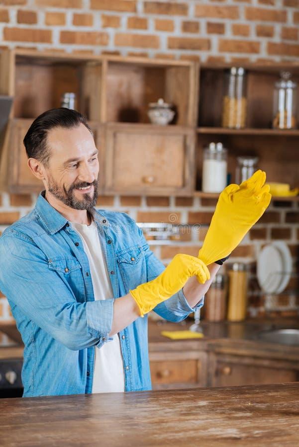 Peinzende mannelijke reinigingsmachine die op gele handschoenen zetten royalty-vrije stock foto's