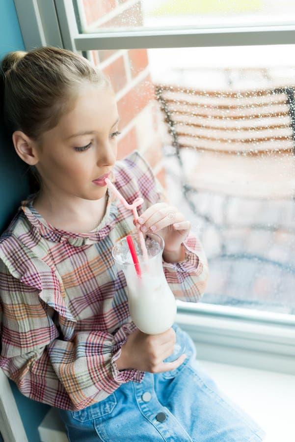 Peinzende meisje het drinken milkshake terwijl het zitten dichtbij venster in koffie stock foto's