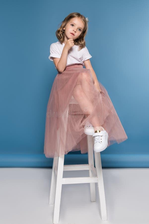Peinzende meisjezitting op ladder en weg het kijken royalty-vrije stock foto's