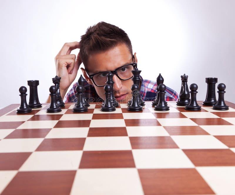 Peinzende mens voor zijn eerste schaakbeweging royalty-vrije stock foto's