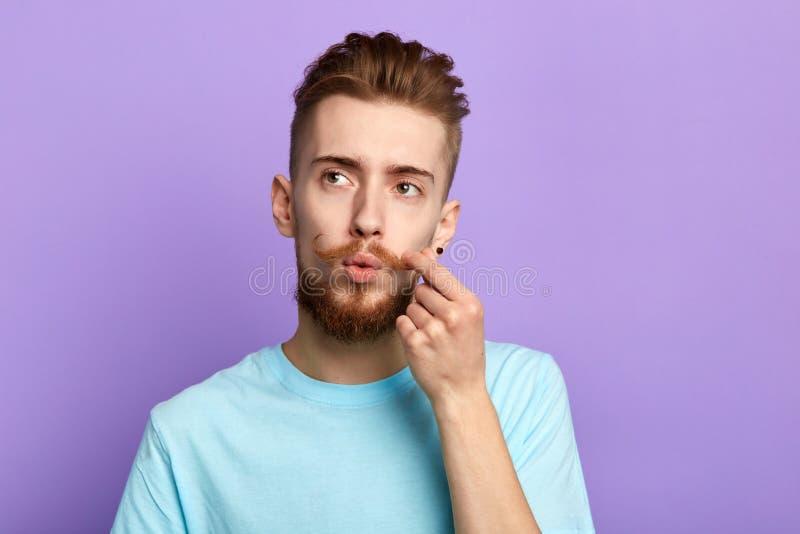 Peinzende, modieuze knappe mens wat betreft zijn snor stock afbeelding