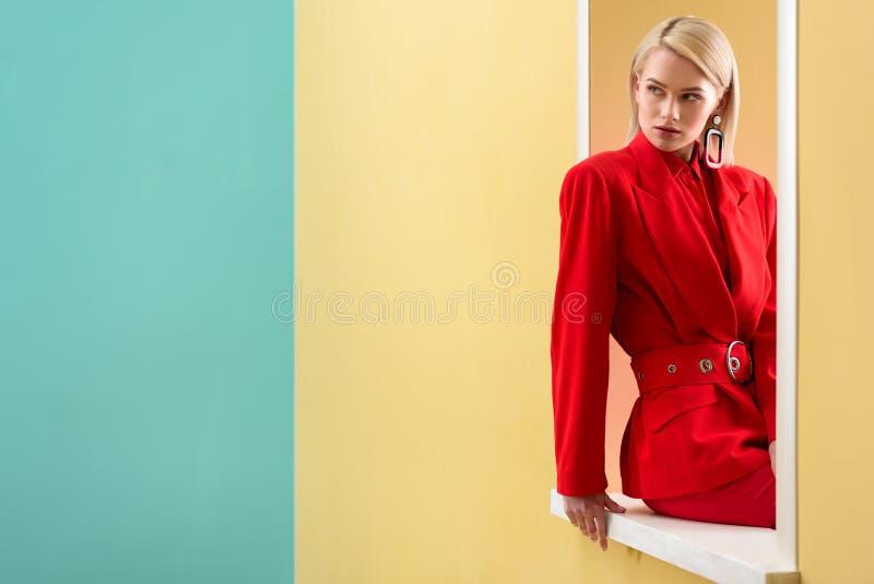 peinzende modieuze vrouw die in rood kostuum uit kijken stock afbeelding