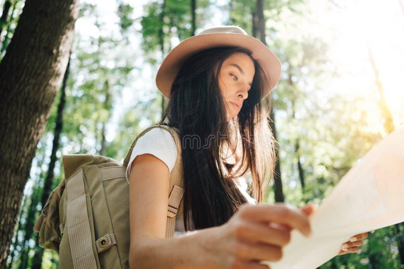 Peinzende moedige vrouw met rugzak die alleen onder bomen in openlucht reizen op Jong reizigersmeisje die in bos en het kijken lo stock foto's