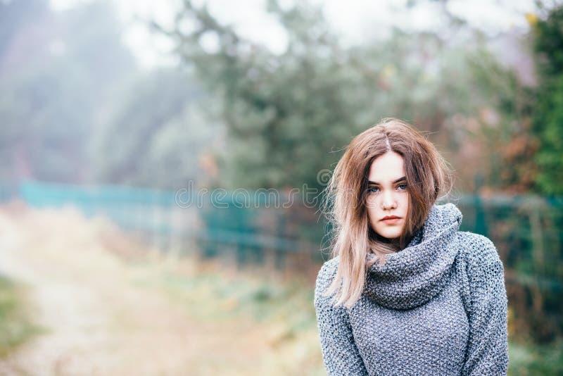 Peinzende mooie jonge vrouw in wollen sweater royalty-vrije stock foto's