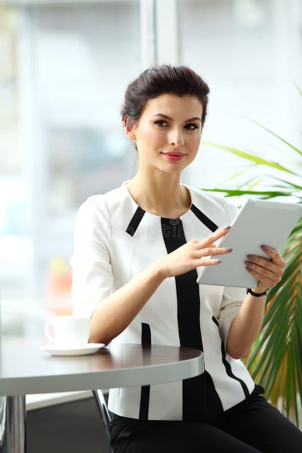 Peinzende onderneemster die een artikel op tabletcomputer lezen royalty-vrije stock afbeeldingen