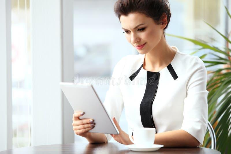 Peinzende onderneemster die een artikel op tabletcomputer lezen royalty-vrije stock foto