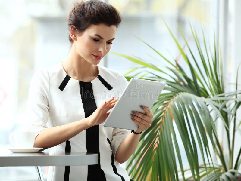 Peinzende onderneemster die een artikel op tabletcomputer lezen stock foto