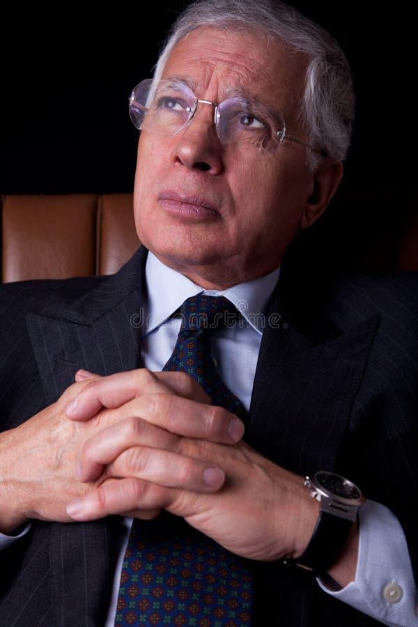 Peinzende rijpe zakenman gezet op een stoel royalty-vrije stock afbeelding
