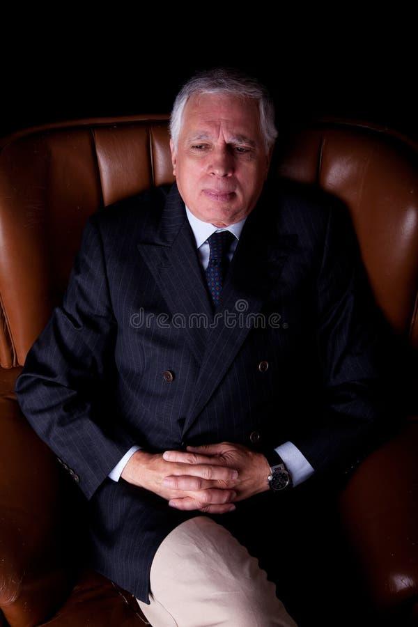 Peinzende rijpe zakenman gezet op een stoel royalty-vrije stock foto's